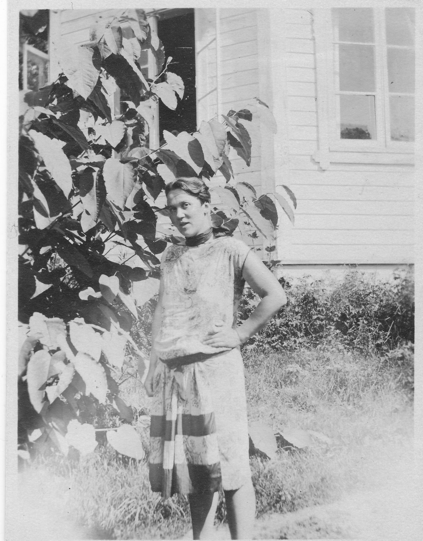 Salme Corner Norrlinin huvilan edustalla 1927. Huvilan puutarhassa kasvoi jättitatar. Kuva: Frithjof Corner